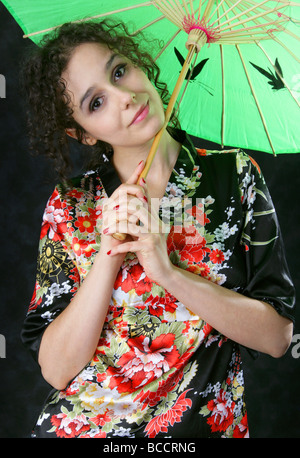 Dark Haired Portuguese Woman Holding a Green Umbrella and Smiling - Stock Image