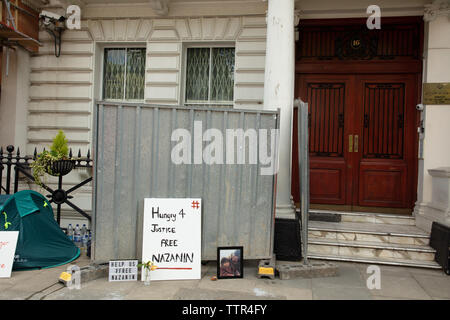 London, UK. 17th June 2019. Tent of Richard Ratcliffe on hunger strike in front of the Iranian embassy in London in protest of the detention of his wife Nazanin Zgahari in Iran over spying allegations. Staff of the embassy and builders have placed iron boards squeezing the protesters' space. Credit: Joe Kuis / Alamy - Stock Image