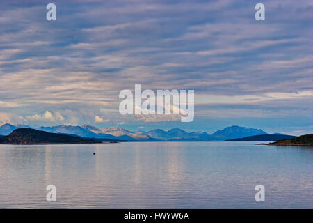 The setting sun illuminates clouds over the sea near Harstad in northern Norway. - Stock Image