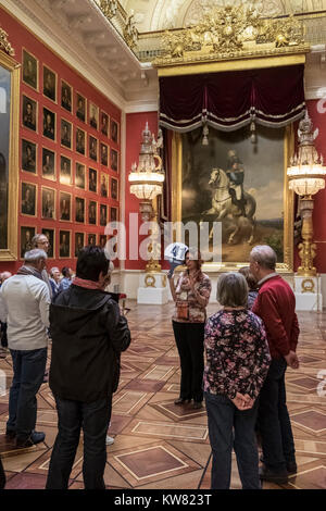 Visitors with tour guide viewing paintings in the 1812 War Gallery at The State Hermitage Museum, Saint Petersburg, - Stock Image