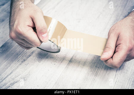 Male Hands Holding An Unrolled Parcel Tape Over Wooden Table - Stock Image