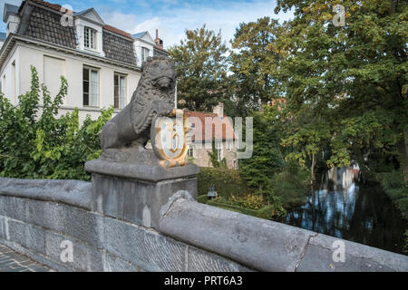 Canal bridge with lion sculpture and coat of arms badge, Bruges, West Flanders, Belgium. - Stock Image