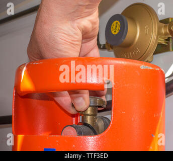 Man's hand turning the tap on a propane gas bottle, with a regulator nearby on the wall, inside the cupboard of a caravan / motorhome. - Stock Image
