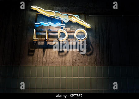 Lido swimming pool sign with a woman diving into wavy water in a neon light style - Stock Image