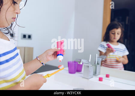 little girl putting toothpaste on the brush, after taking a shower she prepares to brush her teeth in front of the mirror of the bathroom, kids hygien - Stock Image