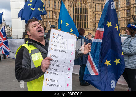 London, UK. 9th January 2019. Protests by stop Brexit group SODEM (Stand of Defiance European Movement) and pro-Brexit campaigners continue opposite Parliament. This man with a poster for the Guy Fawkes Movement promising civil war if we fail to leave the EU shouts insults at SODEM protesters, most of the other s in yellow jackets were fairly subdued. Most Brexiteers had come to support Brexit rather than cause trouble. Credit: Peter Marshall/Alamy Live News - Stock Image