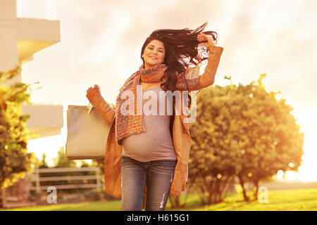 Pregnant woman after shopping, happy expectant girl with paper bags going home, mild sunset light, enjoying great - Stock Image