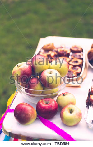 Fresh whole apples in a glass bowl on a table.  - Stock Image