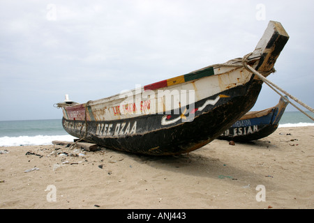 Seagoing dugout canoe parked on beach in between fishing trips Winneba Ghana - Stock Image