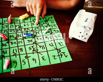 Girl plays her homemade board game with homemade counters and dice. - Stock Image