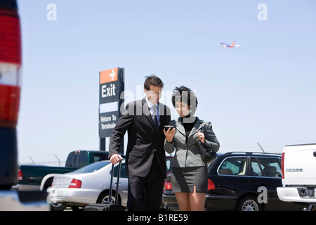 A man and woman carrying a hand held tracking device. - Stock Image