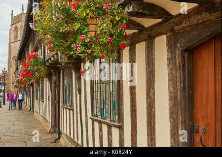 Almshouses decked out with colourful hanging baskets in Stratford upon Avon - Stock Image