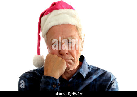 Man in his sixties wearing a cheap 'Santa Hat' looking sad - Stock Image