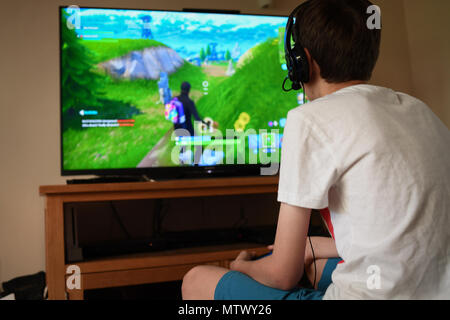 A teenage boy AGE 13plays Fortnite computer game on the PS4 using a headset to communicate with other players in his squad. - Stock Image