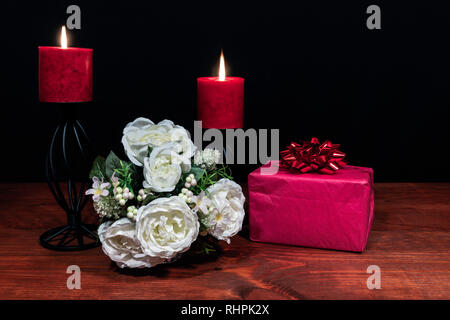 Beautiful bouquet of arranged flowers red candles on a holder with a present on a wooden table. mothers day, Easter, valentines, birthday, Christmas, - Stock Image