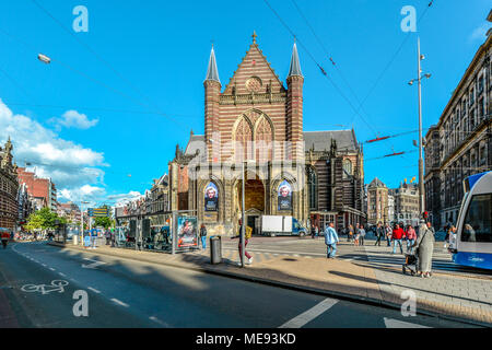 Tourists and locals cross a busy intersection in front of the Nieuwe kerk (New church) located on Dam square in Amsterdam, Netherlands city center - Stock Image