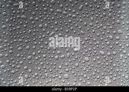 Raindrops on glass Grey - Stock Image