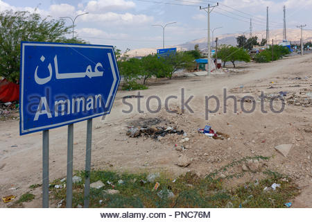 Amman Road Sign Surrounded by Trash and Rubbish - located in the Jordan Valley - Stock Image