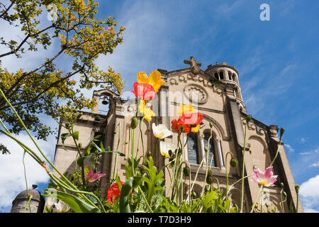 The neo-romanesque facade of the St. Théodorit cathedral at Uzès, France with flowers at the foreground and campanile Tour Fénestrelle in the backgrou - Stock Image