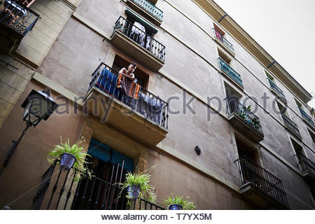 Man standing on balcony outside appartment in  Street in the City of Barcelona in Catalunya in Spain in Europe - Stock Image
