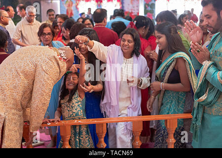 Worshippers sprinkle flower petals on a Hindu man in his fifties who assisted in morning services at his temple to celebrate his birthday. In Queens. - Stock Image