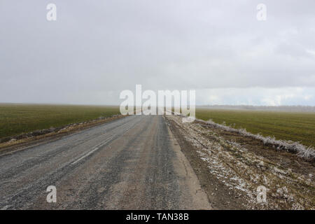 Cloudy weather with snow in the spring, view from the road passing through the fields - Stock Image