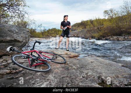 Cyclist at river - Stock Image