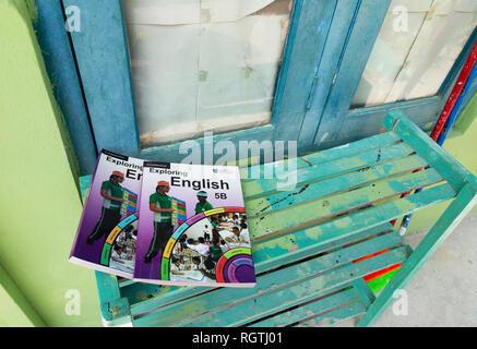 Cambridge Exam Board - English books on a bench in a school in the Maldives, Asia - Stock Image