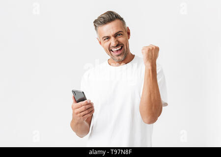 Image of cheery man 30s wearing casual t-shirt rejoicing while using smartphone isolated over white background - Stock Image
