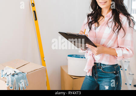cropped view of woman holding clipboard and pencil in hands - Stock Image