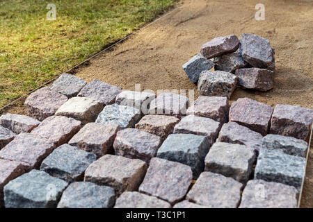 garden path construction - laying granite stone pavers at home backyard - Stock Image