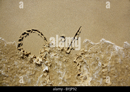 '0%' written out in wet sand, being washed away by the sea. Please see my collection for more similar photos. - Stock Image