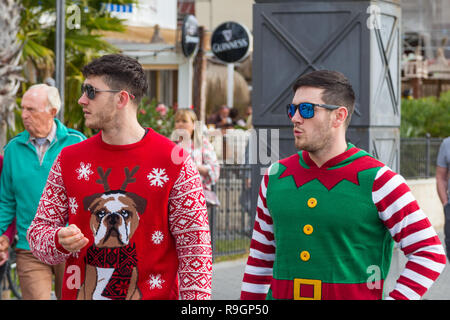Benidorm, Costa Blanca, Spain, 25th December 2018. British tourists dress for the occasion on Christmas Day in this favourite getaway destination for Brits escaping the cold weather at home. Temperatures will be in the mid to high 20's Celsius today in this mediterranean hotspot. Two young men walking along wearing Christmas jumpers looking away from camera. - Stock Image