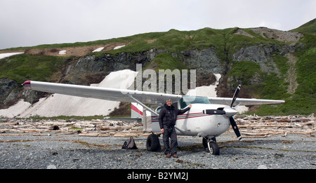 K-Bay Air air plane (Cessna 206) and pilot standing on a gravel beach of the Katmai National Park and Preserve, - Stock Image