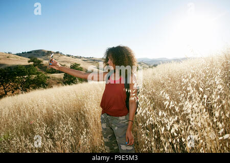 Young woman with curly brown hair hiking in urban park, taking picture with mobile phone. - Stock Image