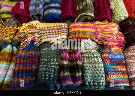 A table full of colorful hand knit winter hats and scarves for sale in Speculator, NY USA for the holiday season. - Stock Image