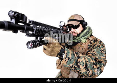 Studio shot of U.S. Marine in uniform, equipped with rifle. - Stock Image
