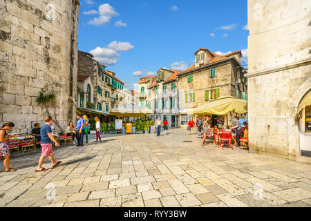 Locals and tourists intermingle on a sunny morning in early autumn at the Fruit Square of Diocletian's Palace in the ancient city of Split, Croatia. - Stock Image
