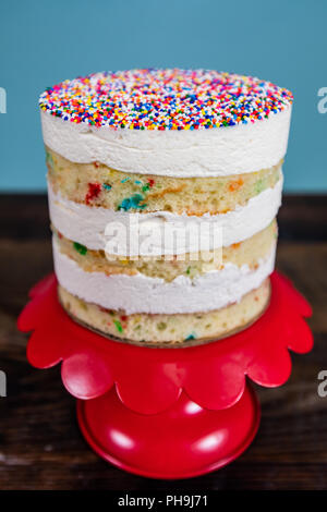 Narrow Focus of Naked Funfetti Cake on red cake stand - Stock Image