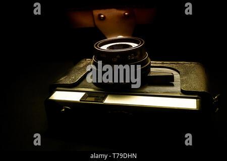 Vintage camera on wooden background,old camera on stiletto - Stock Image