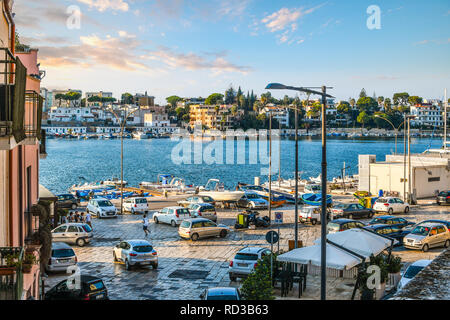Children play among the parked cars on the waterfront promenade of the coastal port city of Brindisi, Italy - Stock Image