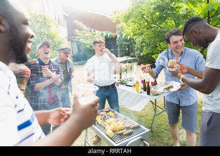 Male friends laughing and eating around barbecue grill in backyard - Stock Image