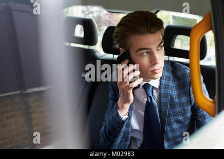 Young businessman on phone in taxi looking out of window - Stock Image