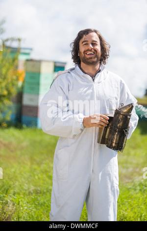 Happy Male Beekeeper Holding Smoker - Stock Image