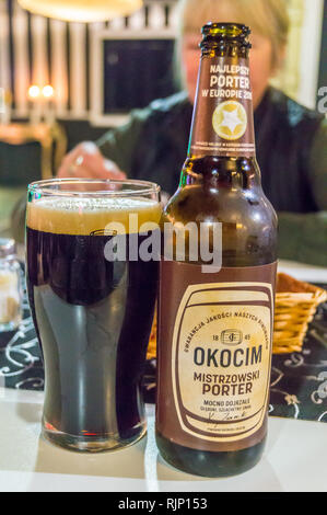 A bottle and branded glass of Okocim Baltic porter beer, Gdańsk, Poland - Stock Image