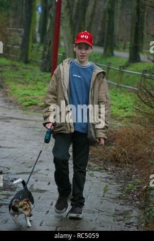 Teenage boy walk the pulling dog on a leash, front view, full body shot, in winter in park. - Stock Image