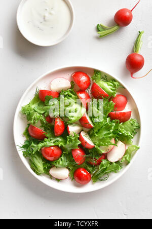 Radish salad with lettuce leaves in bowl over white stone background. Top view, flat lay - Stock Image