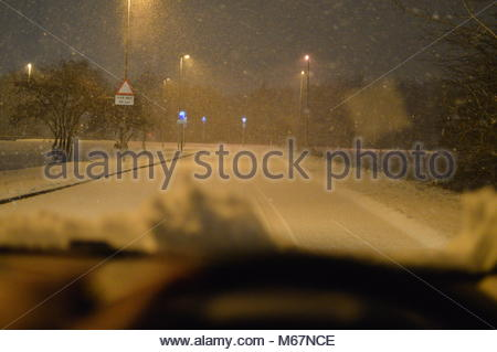 Person drives their vehicle on snow covered roads in the dark at night - Stock Image