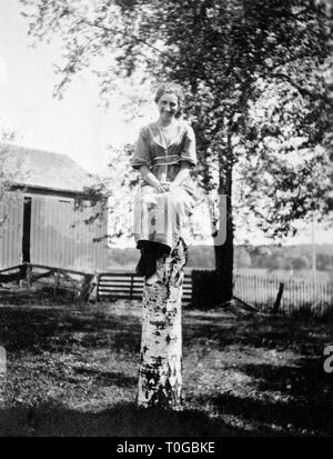 A woman sits atop a birch tree stump in the farmyard, ca. 1920. - Stock Image