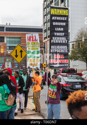 CHARLOTTE, NC, USA-3/16/19: A man points at camera while holding a sign listing behaviors which mean 'Hell Forever'. - Stock Image